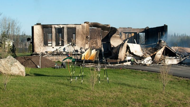 Smoke rises from the remains of houses outside Slave Lake, Alta., on Monday May 16, 2011. (Ian Jackson / CANADIAN PRESS)