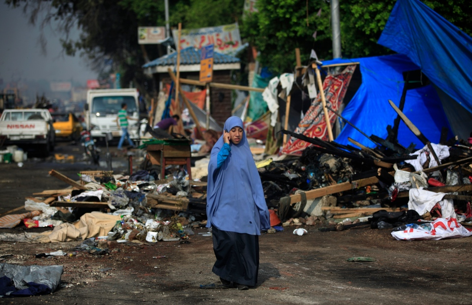 A woman speaks on the phone as she walks next to destroyed tents outside the Rabaah al-Adawiya mosque, where supporters of Egypt's ousted President Mohammed Morsi had a protest camp in Nasr City, Cairo, Egypt, Thursday, Aug. 15, 2013. (AP / Khalil Hamra)