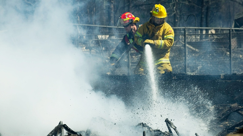 Firefighters work on the smouldering remains of houses in Slave Lake, Alta., on Monday, May 16, 2011.  (Ian Jackson / THE CANADIAN PRESS)