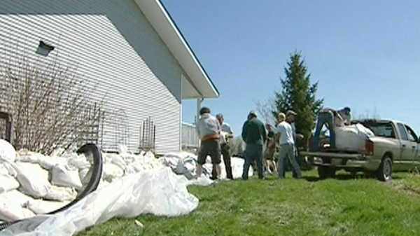 Residents are seen sandbagging a home in Portage la Prairie, Monday, May 16, 2011.