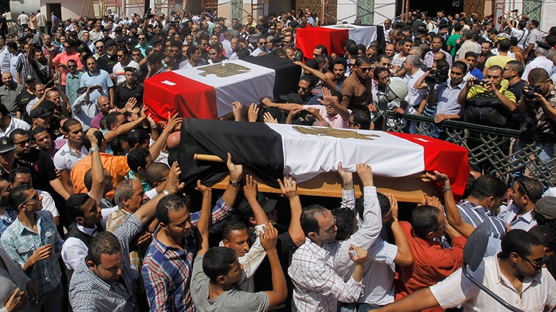 Egyptian relatives and colleagues of policemen who were killed during Wednesday's clashes carry coffins covered with national flags during a military funeral in Cairo, Egypt, Thursday, Aug. 15, 2013. (AP / Amr Nabil)