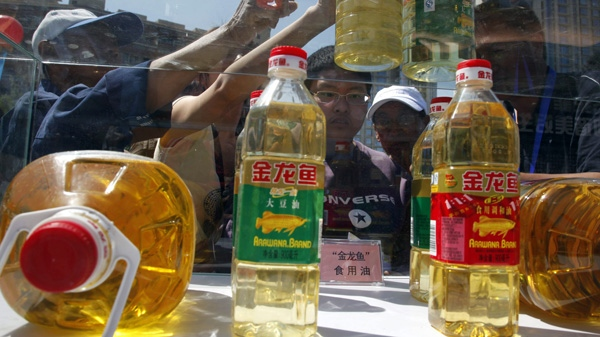 Chinese residents try to tell counterfeit cooking oil products from the real products during an event to promote awareness of economic crimes in Beijing, China, Sunday, May 15, 2011. (AP Photo/Ng Han Guan)