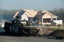 The smouldering remains of houses are visible outside Slave Lake, Alta., Monday, May 16, 2011. A firestorm swept through the town of 7,000 destroying upwards of 30 percent of the buildings. (Ian Jackson / THE CANADIAN PRESS)