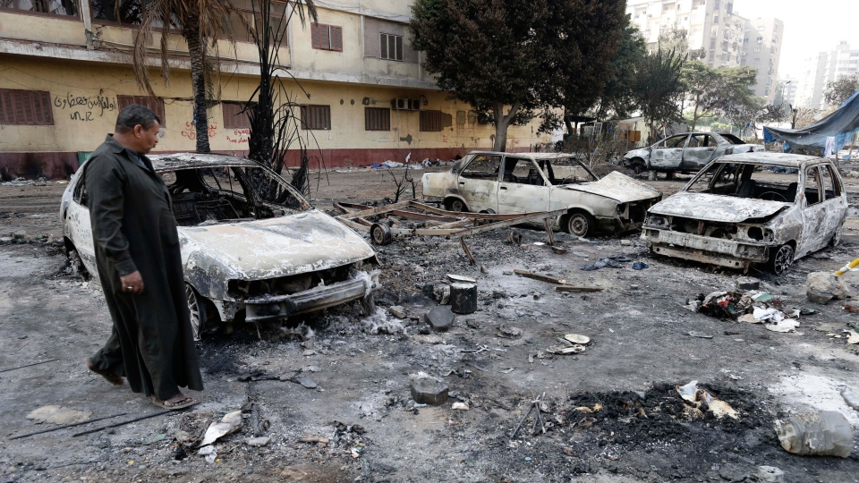 An Egyptian man walks through debris from what is left of burned vehicles outside the Rabaah al-Adawiya mosque in the district of Nasr City, Cairo, Egypt, Friday, Aug. 16, 2013. (AP / Hassan Ammar)