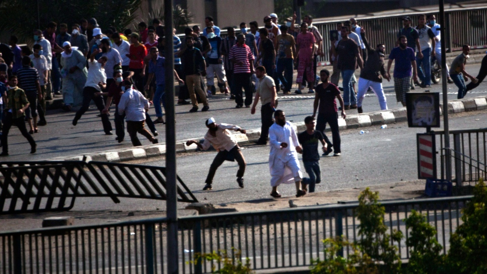 Supporters of ousted Egyptian President Mohammed Morsi throw stones against other civilians in Cairo, Friday, Aug. 16, 2013. (AP / Manu Brabo)