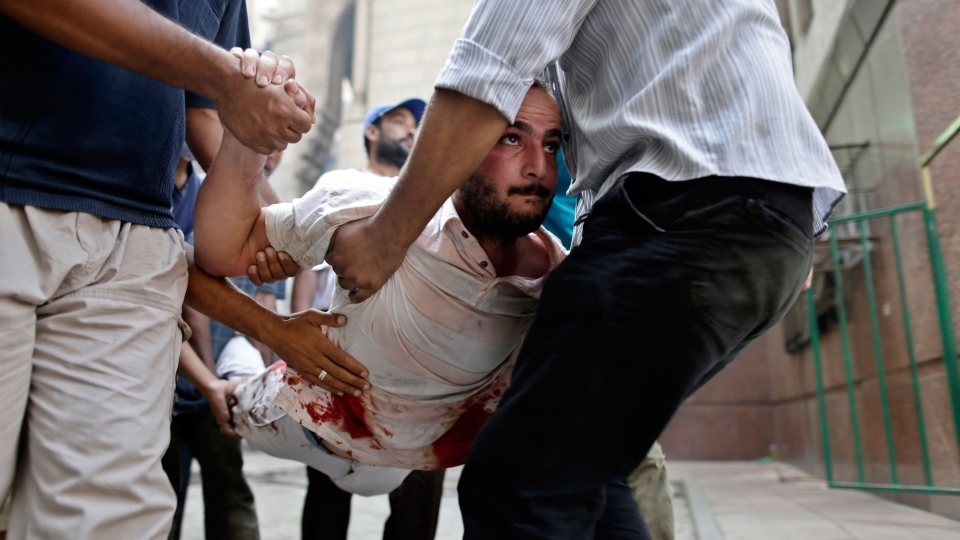 Supporters of Egypt's ousted President Mohammed Morsi evacuate a wounded man during clashes with Egyptian security forces in Ramses Square, in downtown Cairo, Egypt, Friday, Aug. 16, 2013. (AP / Hassan Ammar)