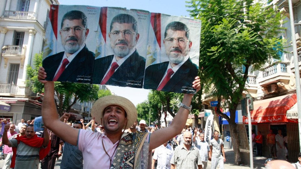 A demonstrator holds portraits of ousted Egyptian president Mohamed Morsi during a public gathering in Tunis, Tunisia, Friday Aug. 16, 2013, in support of Morsi. (AP / Amine Landoulsi)