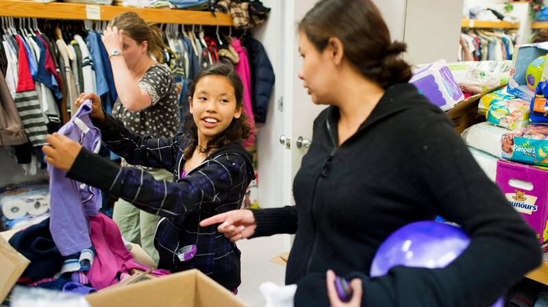 Rayna Auger, right, and daughter Meggie, 10, look through donated clothes at the Westlock and District Community Hall in Westlock, Alberta, on Monday, May 16, 2010, after being evacuated from Slave Lake, Alta. (John Ulan / THE CANADIAN PRESS)