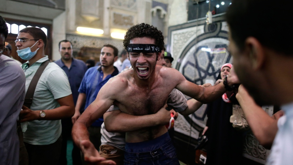 Egyptians restrain a man mourning over the body of a relatives in the Al-Fath mosque, in downtown Cairo, Egypt, Friday, Aug. 16, 2013. (AP / Hassan Ammar)