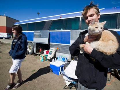 Chris Radis holds his cat Kratos as his girlfriend Lisa Lazaruk lloks on at the evacuee centre Athabasca, Alta., on Tuesday, May 17, 2011. An emergency official says there's no timeline as to when residents will be able to return to a northern Alberta town scorched by a forest fire. (THE CANADIAN PRESS\Ian Jackson)