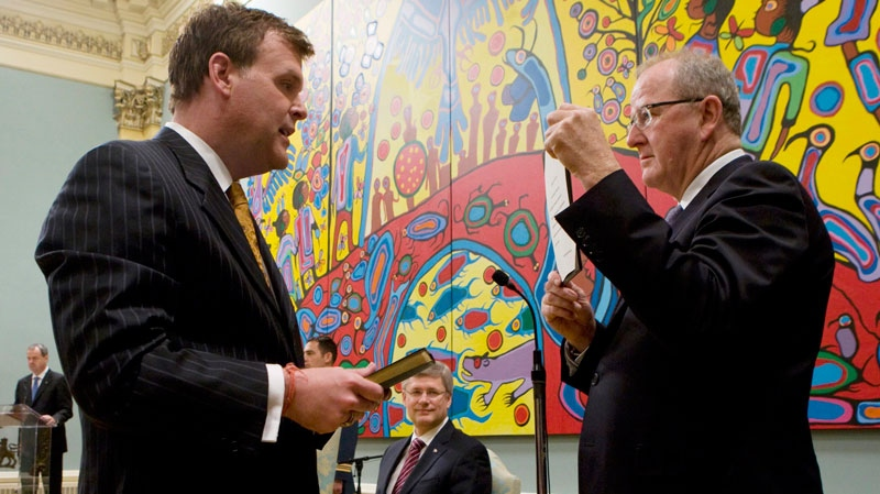 Minister of Foreign Affairs John Baird is sworn in by Clerk of the Privy council Wayne Wouters as Prime Minister Stephen Harper looks on, during a ceremony at Rideau Hall in Ottawa, Wednesday, May 18, 2011. (Adrian Wyld / THE CANADIAN PRESS)
