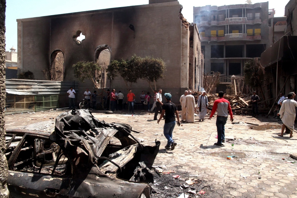 Egyptian gather in the ruins of the Evangelical Church of Malawi after it was ransacked, looted and burned by an angry mob, in Malawi, south of Minya, Egypt, Saturday, Aug. 17, 2013. (Roger Anis / El Shorouk Newspaper)