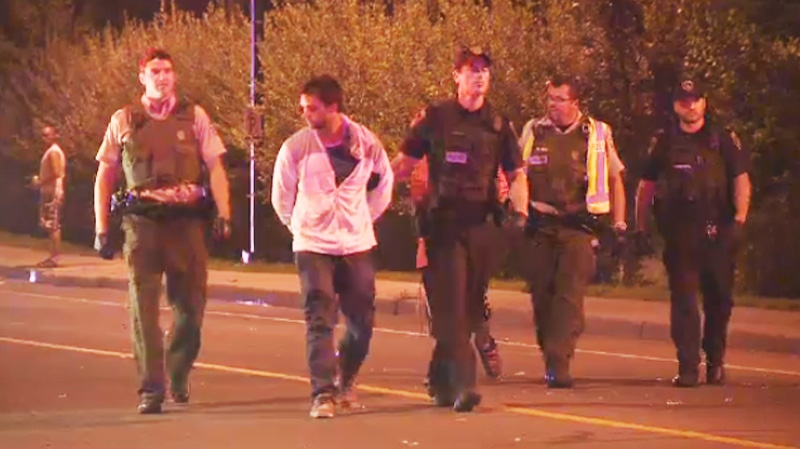 Police are seen here escorting one man away from the riot in Blainville Saturday night, Aug. 17, 2013.