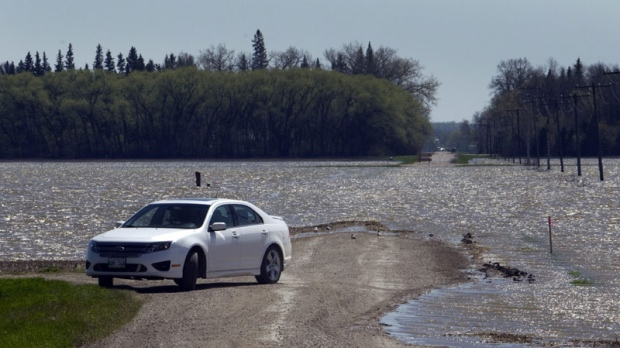 A car turns around as the waters from the Assiniboine River breach flood across a road Tuesday, May 17, 2011 near Newton, Manitoba. (THE CANADIAN PRESS/Ryan Remiorz)