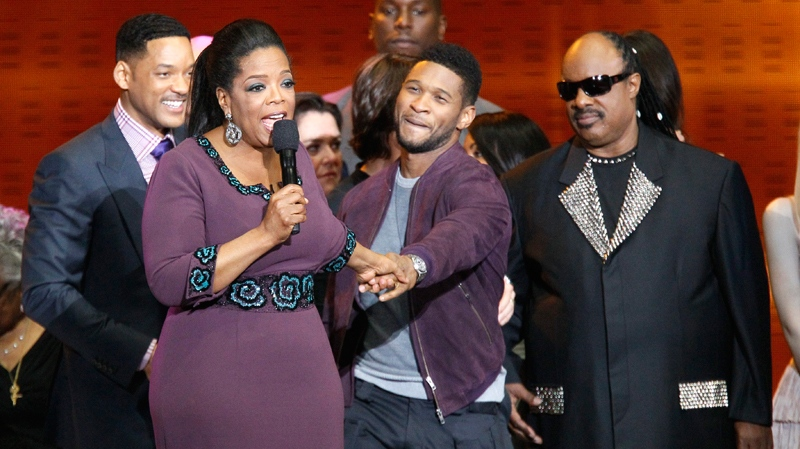 Oprah Winfrey acknowledges fans as she is surrounded by stars during a star-studded double-taping of 'Surprise Oprah! A Farewell Spectacular, Tuesday, May 17, 2011, in Chicago. (AP / Charles Rex Arbogast)