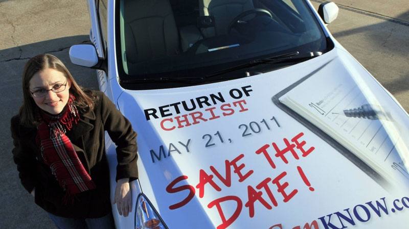 FILE - In this Dec. 17, 2010 file photo, Allison Warden poses with her car in Raleigh, N.C., showing a message about the rapture. Warden has been helping organize a campaign using billboards, post cards and other media in cities across the U.S. through the website We Can Know. (AP Photo/Gerry Broome, File)