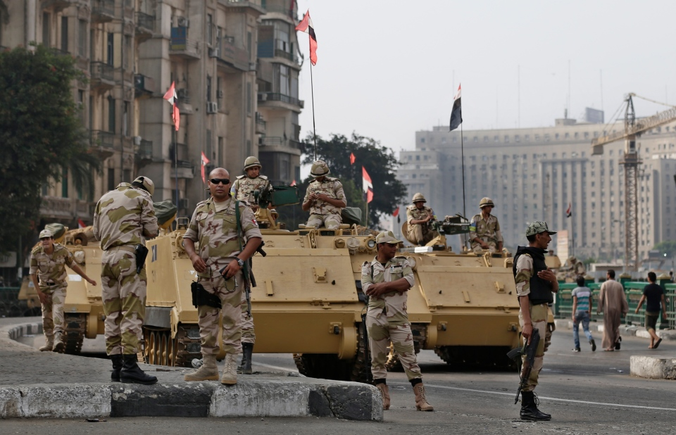 Egyptian army soldiers take their positions on top and next to their armored vehicles while guarding an entrance of Tahrir square, in Cairo, Egypt on Aug. 16, 2013. (AP / Hassan Ammar)