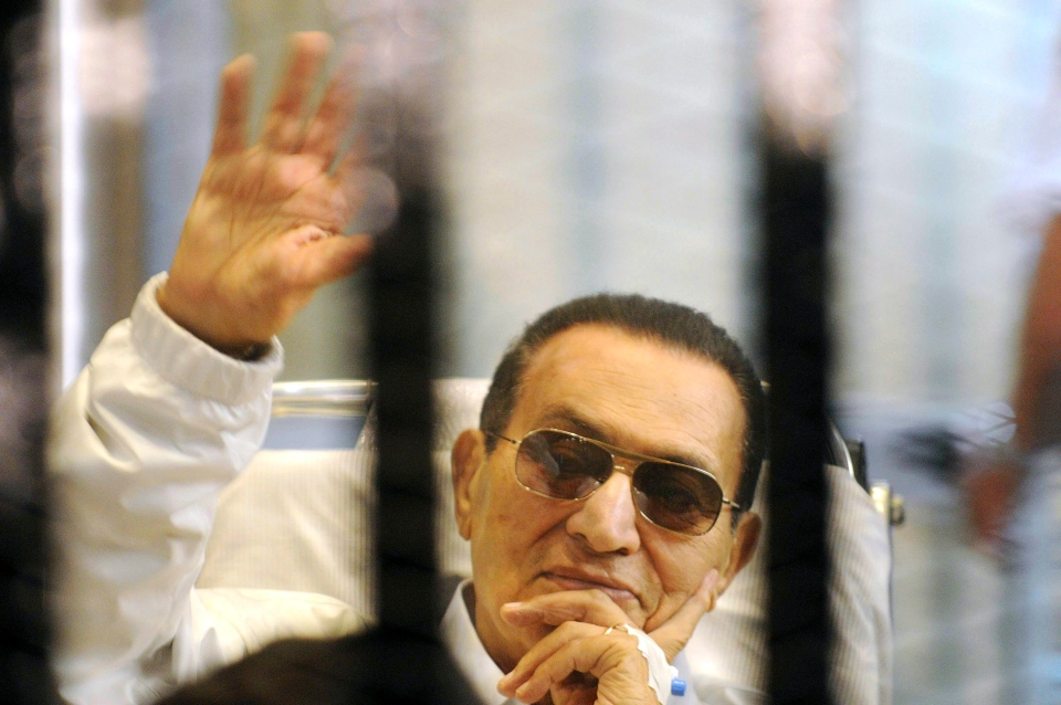 Former Egyptian president Hosni Mubarak waves to his supporters from behind bars as he attends a hearing in his retrial in Cairo, Egypt, Saturday, April 13, 2013. (AP)