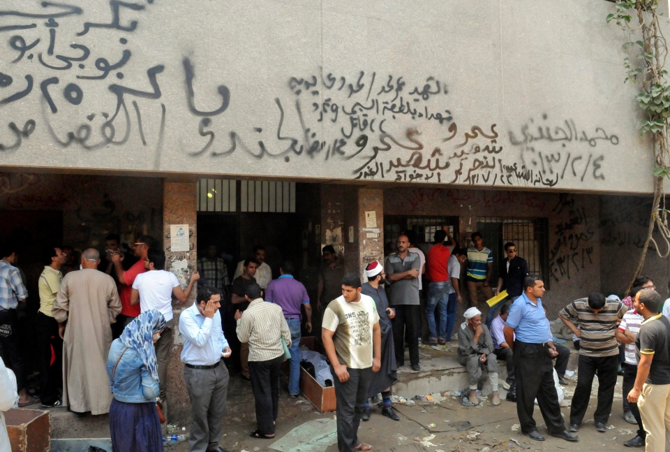 People gather at the Zenhoum morgue to identify loved ones and retrieve their bodies for burial following the deaths of hundreds of people in violence over the last week, in Cairo, Egypt, Monday, Aug.19, 2013. (AP / Mohammed Assad)