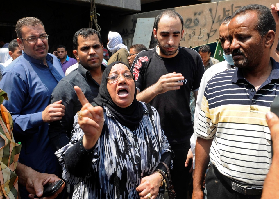 People gather at the Zenhoum morgue to identify loved ones and retrieve their bodies for burial following the deaths of hundreds of people in violence over the last week, in Cairo, Egypt, Monday, Aug. 19, 2013. (AP / Mohammed Assad)