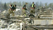 Workers sift through the aftermath of wildfires in Slave Lake, Alta., Thursday, May 19, 2011.