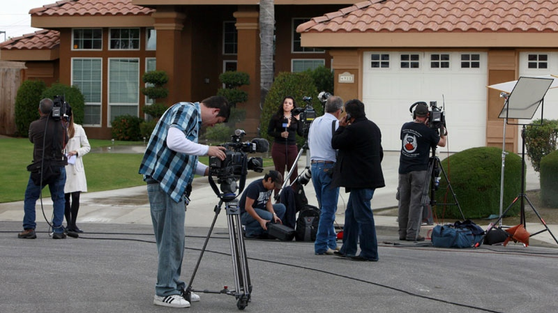 News media are shown outside the home believed to be the residence of a household staff member who mothered a child with former Gov. Arnold Schwarzenegger, Wednesday, May 18, 2011, in Bakersfield, Calif. (AP Photo/Nick Ut)