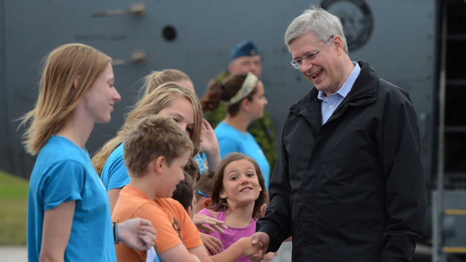 Prime Minister Stephen Harper is welcomed by summer camp kids as he arrives in Hay River, Northwest Territories on Monday, Aug. 19, 2013. (Sean Kilpatrick / THE CANADIAN PRESS)