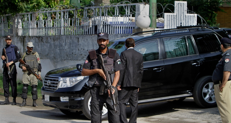 A Pakistani police commando and paramilitary soldiers stand guard as a vehicle carrying former President and army chief Pervez Musharraf leaves from an anti terrorism court in Rawalpindi, Pakistan, Tuesday, Aug. 20, 2013. (AP / Anjum Naveed)