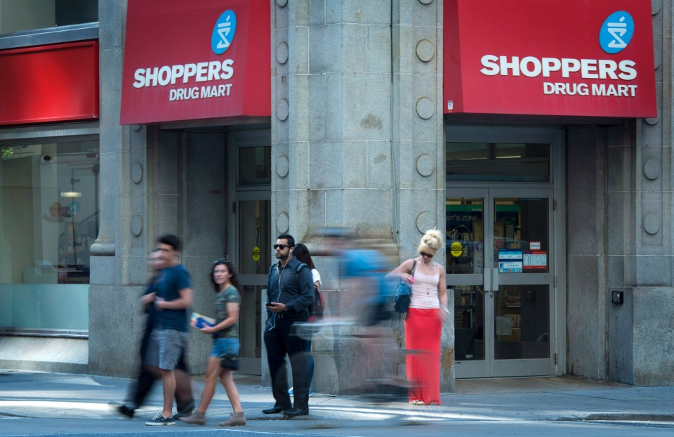 People pass by a Shoppers Drug Mart in downtown Toronto on Monday, July 15, 2013. (Graeme Roy /The Canadian Press)