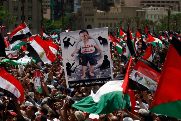 """An Egyptian man holds a caricature picture of deposed President Hosni Mubarak with Arabic word reading, """"search me,"""" during a rally in Tahrir square in Cairo, Egypt Friday May 13, 2011. (AP / Khalil Hamra)"""