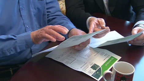 Former politician Tim Hudak looks at a hydro bill with a Ontario resident in this file photo.