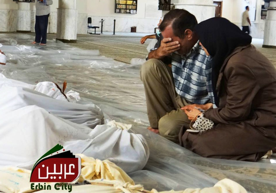 In this citizen journalism image provided by the Local Committee of Arbeen, which has been authenticated based on its contents and other AP reporting, a man and woman mourn over the dead bodies of Syrian men after an alleged poisonous gas attack fired by regime forces, according to activists in Arbeen town, Damascus, Syria, Wednesday, Aug. 21, 2013.