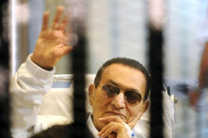Former Egyptian President Hosni Mubarak waves to his supporters from behind bars as he attends a hearing in his retrial on appeal in Cairo, Egypt, in this Saturday, April 13, 2013 file photo. (AP / File)