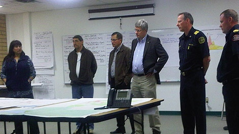 Prime Minister Stephen Harper and Alberta Premier Ed Stelmach meet with emergency officials in Slave Lake, Alta. on Friday, May 20, 2011. (Government of Alberta)