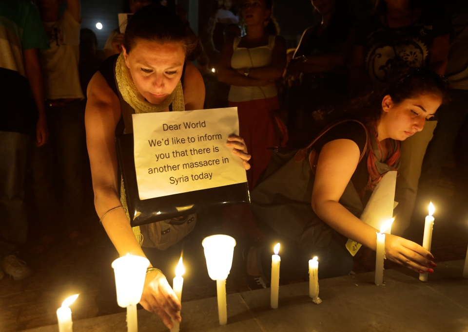 Syrian women who live in Beirut, light candles during a vigil against the alleged chemical weapons attack on the suburbs of Damascus, in front the United Nations headquarters in Beirut, Lebanon, Wednesday, Aug. 21, 2013. (AP / Hussein Malla)