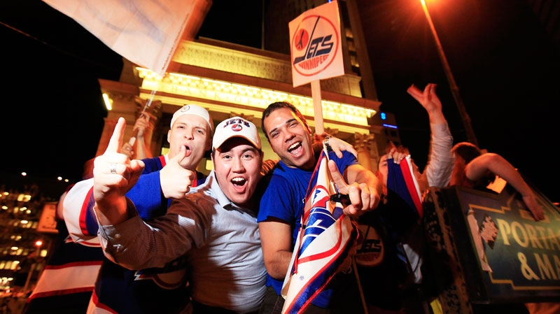 Hockey fans celebrate at Portage and Main in downtown Winnipeg after reading a report that a NHL team maybe returning to Winnipeg, Thursday, May 19, 2011. (John Woods / THE CANADIAN PRESS)