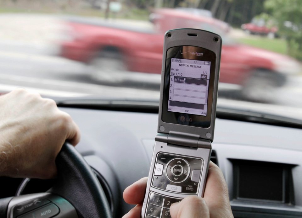 A phone is held in a car in Brunswick, Maine, Sept. 20, 2011. (AP / Pat Wellenbach)