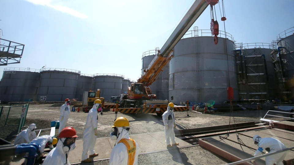 Workers wearing protective gears take a survey near tanks of radiation contaminated water at Tokyo Electric Power Co.'s Fukushima Dai-ichi nuclear power plant in Okuma town, Fukushima prefecture, northeast of Tokyo. (AP / Issei Kato, Pool, File)