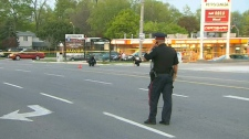 A police officer surveys the scene of a gas robbery in Mississauga that sent an attendant to hospital in critical condition, Friday, May 20, 2011.