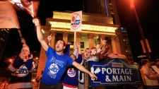 Hockey fans celebrate at Portage and Main in downtown Winnipeg after reading a report in The Globe and Mail newspaper that a NHL team maybe returning to Winnipeg, Thursday, May 19, 2011. (John Woods / THE CANADIAN PRESS)
