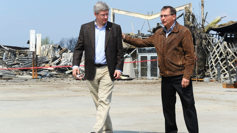 Prime Minister Harper and Alberta Premier Ed Stelmach talk as they tour the devastation in Slave Lake, Alta., on Friday, May 20, 2011. (Ian Jackson / THE CANADIAN PRESS)