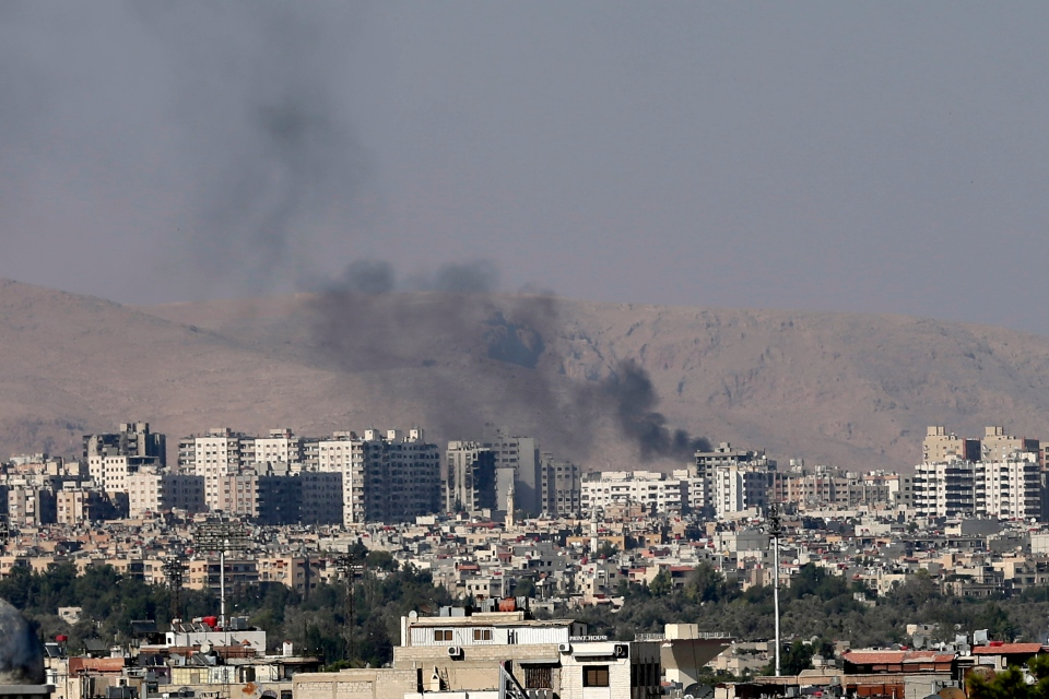 Black columns of smoke from heavy shelling in Barzeh, a suburb of Damascus, Syria, Friday, Aug. 23, 2013. (AP / Hassan Ammar)