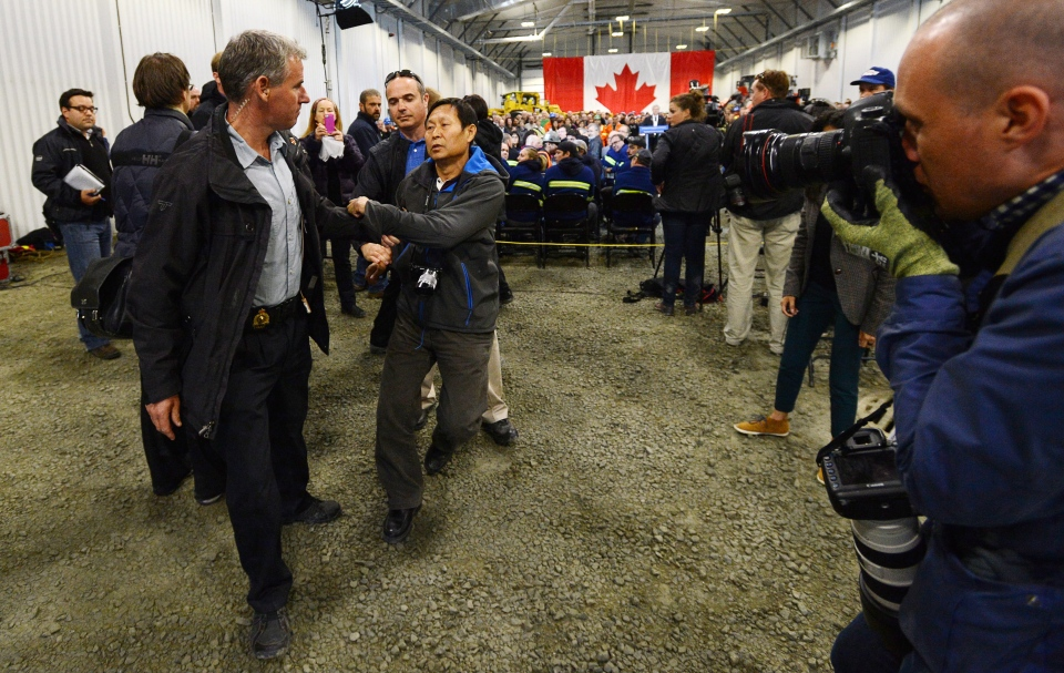 Li Xue Jiang, of the People's Daily, China's largest newspaper, is hauled to the back of the room by RCMP as Stephen Harper answers questions while visiting Xstrata Nickel's Raglan Mine in the northern Nunavik region of Quebec on Friday, August 23, 2013. (Sean Kilpatrick / THE CANADIAN PRESS)