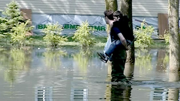 A man carrying a young boy on his shoulders is seen walking through flooded waters in Quebec, Saturday, May 21, 2011.