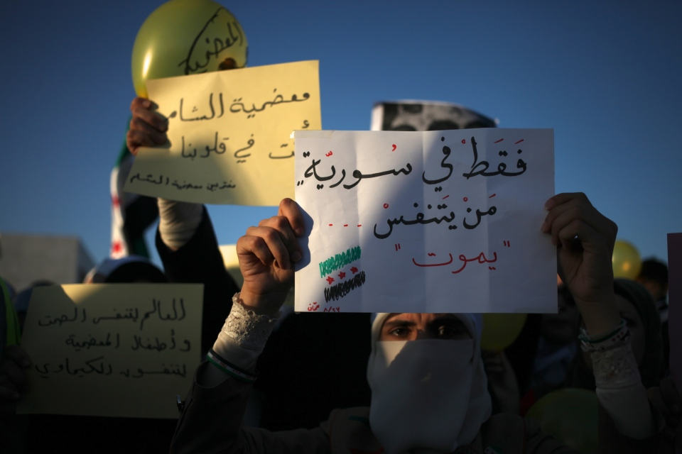 "Syrian veiled woman holds a white placard reading in Arabic "" Only in Syria if you breathe you will die."" and the other yellow placards reads in Arabic "" the world breaths the silence and our babies breath the chemicals."" during a protest in front of the Syrian embassy to condemn the alleged poison gas attack on the suburbs of Damascus, in Amman, Jordan, Friday, Aug. 23, 2013. (AP / Mohammad Hannon)"
