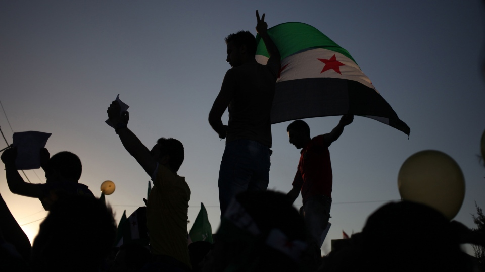 Syrians wave the Syrian revolutionary flag during a protest in front of the Syrian embassy in Amman, Jordan, to condemn the alleged poison gas attack on the suburbs of Damascus, Friday, Aug. 23, 2013. (AP / Mohammad Hannon)