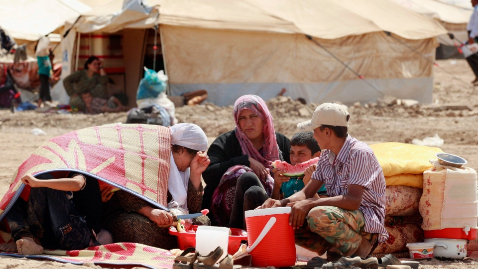 Syrian refugees wait to receive a tent at Kawergost refugee camp in Irbil, 217 miles (350 kilometers) north of Baghdad, Iraq, Wednesday, Aug. 21, 2013. (AP / Hadi Mizban)