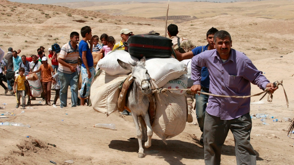 Syrian refugees cross into Iraq at the Peshkhabour border point in Dahuk, 260 miles (430 kilometers) northwest of Baghdad, Iraq, Tuesday, Aug. 20, 2013. (AP / Hadi Mizban)