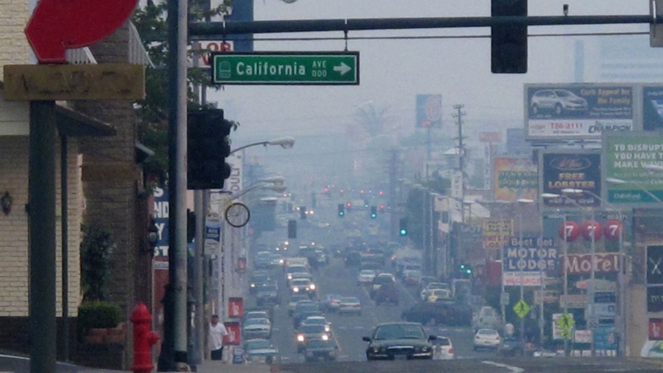"""A smoky haze blankets Virginia Street headed south from the main downtown casino strip near California Street as health district officials raised an air quality alert to the """"red"""" unhealthy level, Friday afternoon, Aug. 23, 2013 in Reno, Nev. (AP / Scott Sonner)"""