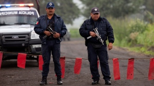 Municipal police guard the entrance to Rancho La Mesa where a mass grave was found in the municipality of Tlalmanalco, Mexico, Thursday, Aug. 22, 2013. (AP / Ivan Pierre Aguirre)